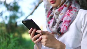Muslim girl with cell in the park. Muslim girl relaxing outdoor and chatting in online messenger on mobile. Hands view with following close-up portrait of woman stock video footage