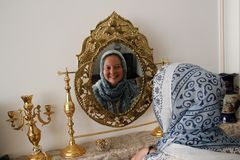Muslim girl with covered head in a blue scarf laughs and smiles and looks in the mirror stock photography