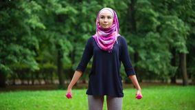 Muslim girl exercising with dumbbells outdoor stock footage