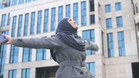 Muslim girl gets excited after read good news on phone, equal rights and freedom. Stock footage stock video