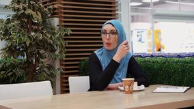 Muslim girl with glasses in a cafe drinks coffee and eats. Leisure, free time, day off stock video