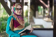 Muslim girl with glasses and veil holding opened book at park stock photo