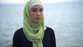 Muslim girl in green hijab against the sea stock footage