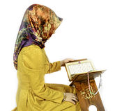 Muslim girl in hijab reading Al Quran on a white background Stock Photography