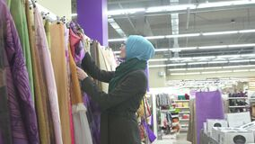 Muslim girl housewife in blue hijab and glasses selects fabrics at hardware store. Muslim girl housewife in blue hijab and glasses selects fabrics stock video footage