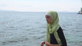 Muslim girl jogging along the sea stock video footage
