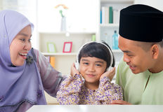 Muslim girl listening to music. At home. Southeast Asian family living lifestyle. Happy smiling Malay parents and child Royalty Free Stock Photos