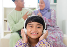 Muslim girl listening to song. At home. Southeast Asian family living lifestyle. Happy smiling Malay parents and child Stock Image