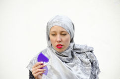 Muslim girl looking at herself in the mirror Stock Photography