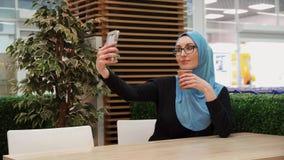 Muslim girl making selfie in cafe. Muslim girl student,Arabic stock footage