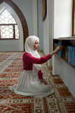 Muslim girl in mosque reading Koran Royalty Free Stock Photography