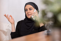 Muslim girl and phone Stock Images
