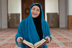 Muslim girl reading Koran Stock Images