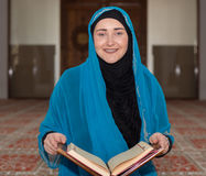 Muslim girl reading Koran Stock Image