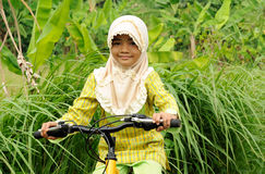 Muslim Girl Riding Bicycle. Indonesian village girl riding bicycle wearing hijab Royalty Free Stock Photography