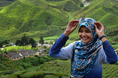 Muslim girl smiling near tea plantations Stock Photo