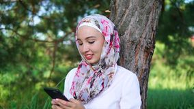 Muslim girl spending outdoor leisure with cell stock footage