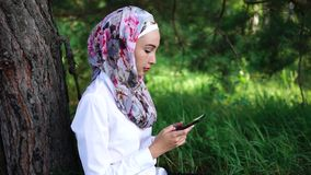 Muslim girl spending outdoor leisure with cell stock video