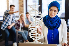 Muslim girl studying genetics. Involved in research. Pleasant muslim women sitting at the table and learnign genetics while her groupmates humiliating her royalty free stock images