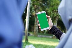 Muslim girl taking selfie with green screen smartphone at public park. Unrecognizable Muslim girl wearing hijab taking selfie with green screen smartphone at Royalty Free Stock Images