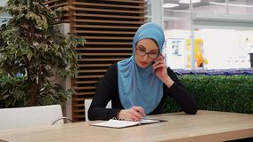 Muslim girl talking on the phone and writing in a notebook. Arabic business lady stock video footage