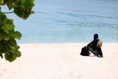 Muslim girl traveler on hijab sitting on the beach royalty free stock photos