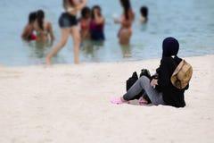 Muslim girl traveler on hijab sitting on the beach royalty free stock image