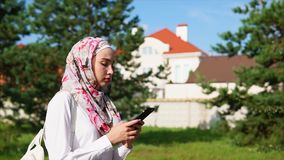 Muslim girl using cell on the go stock video