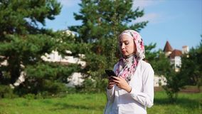Muslim girl using cell on the go. Slow motion steadicam shot of a modern Muslim girl having a walk outdoor and typing on smart phone on the go stock video footage
