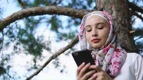 Muslim girl using cellphone in the park stock video