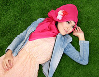Muslim girl wearing hijab lying on grass Royalty Free Stock Photography