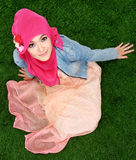 Muslim girl wearing hijab sitting on grass Royalty Free Stock Photos