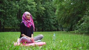 Muslim girl working out in the park stock video