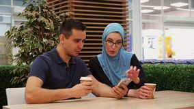 Muslim girl and young man having fun talking in cafe. Close up stock footage