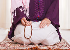 Muslim girl. Young muslim girl with rosary praying on white background stock images