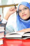 Muslim girls with a book. A young muslim girls was thinking while reading a book Stock Image