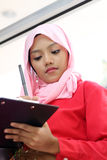 Muslim girls writing on report file Stock Images