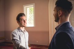 Muslim greeting. Young Muslim men greeting eachother in a mosque Stock Photos