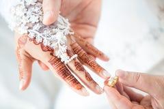 Muslim groom wears the ring bride.  Royalty Free Stock Photos