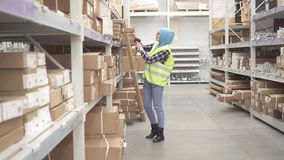 Muslim in a hijab holds inventory with barcode scanner. Muslim woman in a hijab holds inventory with barcode scanner stock footage