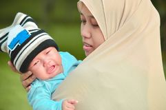 Muslim hijabi mother calming his crying infant baby in her arm at outdoor park in sunny day stock photo