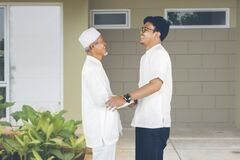Muslim Indonesian father greets son arriving at the house
