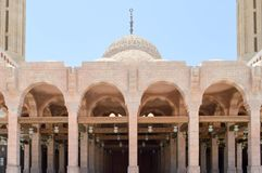 Muslim Islamic Arabian mosque made of white brick for praying architectural construction with arches, domes and carved triangular. Windows Royalty Free Stock Photography