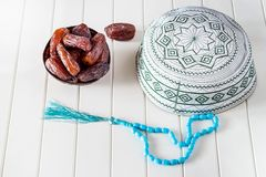 Muslim islamic concept taqiyah skullcap, blue rosary and dates medjul in coconut shel bowl. White wooden background Royalty Free Stock Photography