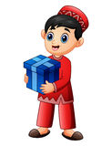 Muslim kid holding red gift box wearing red clothes Stock Photo
