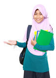 Muslim kid student presenting. Portrait of happy muslim kid student holding books presenting something on white background Royalty Free Stock Photo
