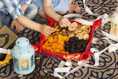 Muslim kids eating iftar breakfast in holy month Ramadan. Muslim kids eating iftar breakfast - Ramadan food - dates , apricots, figs, and palms in the holy month royalty free stock photo