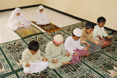 Muslim Kids Praying. At Islamic school stock photos