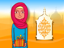 Muslim lady and Arabic text for Eid Mubarak celebration. Arabic Islamic calligraphy of text Eid Mubarak on paper cutout lamp with illustration of a young Muslim Royalty Free Stock Photography