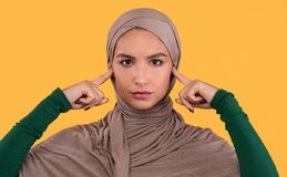 Free Muslim Lady Covering Ears Not Listening Others Opinions, Yellow Background Stock Photography - 201344522